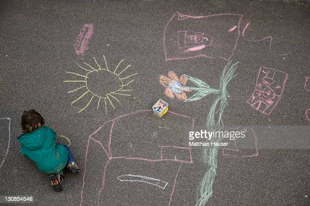 Child is drawing on the street with colorful colourful chalks