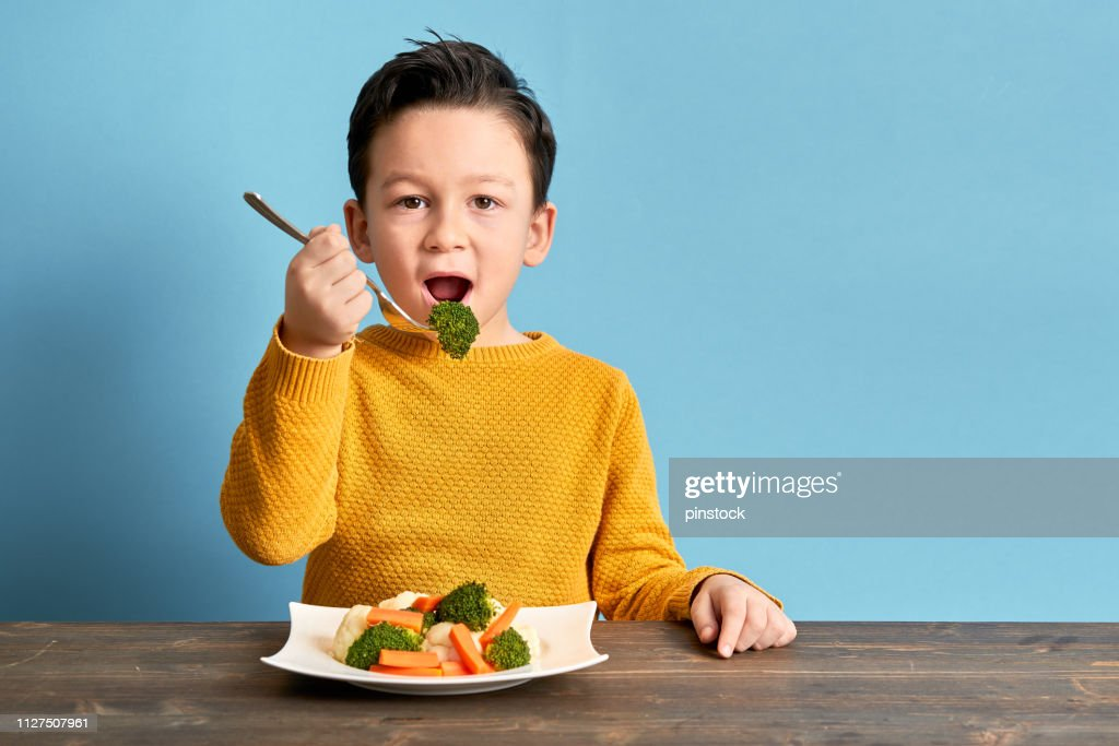 Child is eating vegetables. : Stock Photo