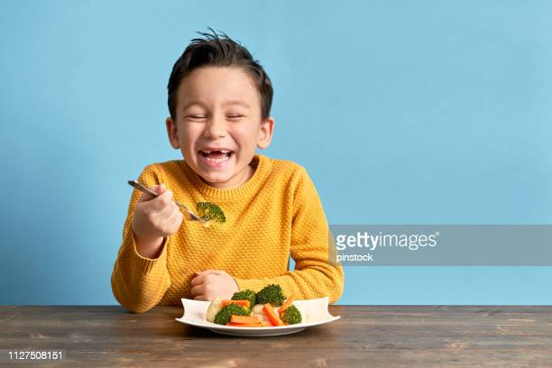child is eating vegetables. - eating stock pictures, royalty-free photos & images