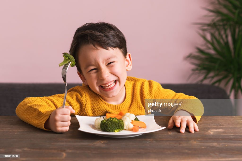 Criança é comer legumes. : Foto de stock
