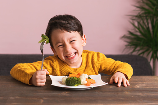 Child is eating vegetables. 904661696