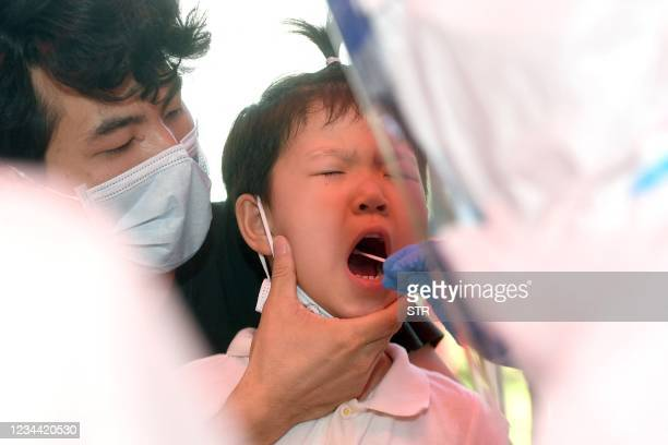 Child is given a nucleic acid test for the coronavirus in Wuhan in China's central Hubei province on August 3 as the city tests its entire population...