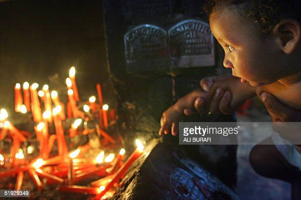 A child is held by his mother as he looks at candles in the sanctury of Gauchito Gil near Mercedes in the Argentine province of Corrientes 08 January...