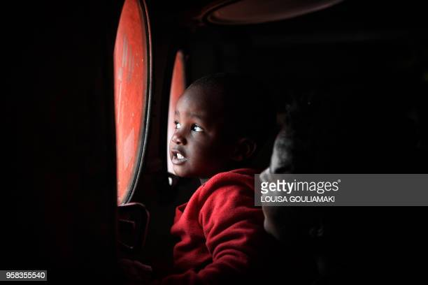 TOPSHOT A child is held up to look out from a porthole on the MV Aquarius upon its arrival at the Sicilian port of Messina on May 14 2018 On May 12...