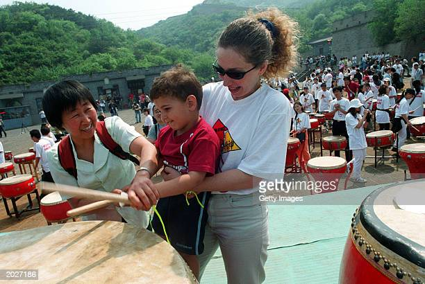 A child is helped by his mother and a Chinese woman to play drums at the 'we shall overcome'ceremony at the Great Wall May 24 2003 in Badaling...