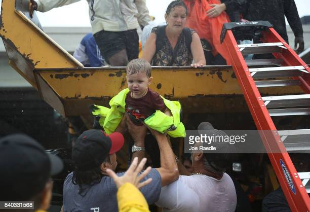 A child is helped off the back of a rescue truck after his family evacuated their home after it was inundated with flooding from Hurricane Harvey on...