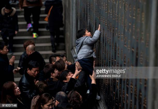 A child is hoisted up to try and touch characters to bring luck for the New Year during a visit to Lingyin Temple in Hangzhou in eastern China's...