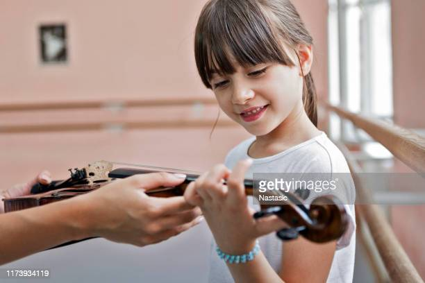 child is introduced with violin in music school - classical concert stock pictures, royalty-free photos & images