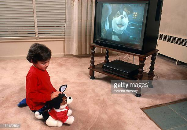 A child is photographed May 12 1993 in New York City playing with 'Toby Terrier' an interactive toy dog programmed to make various comments and...