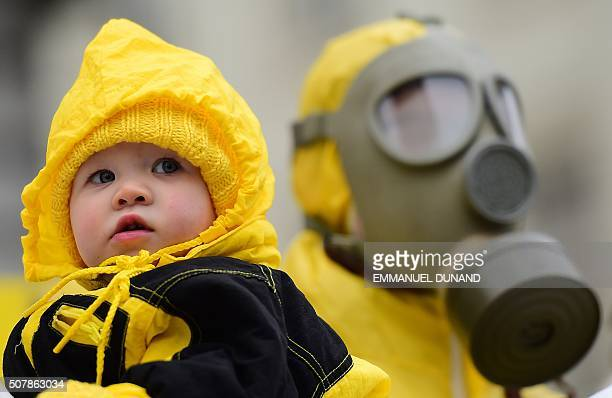 A child is pictured next to an antinuclear activist wearing a gas mask during a protest against the lack of safety of Belgian nuclear power plants...