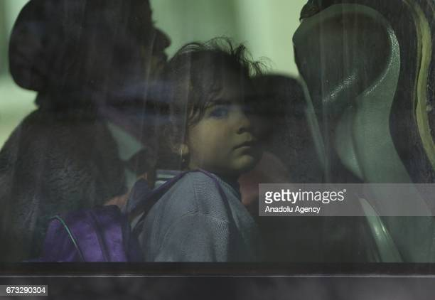 A child is seen in a bus as 250 Iraqi people who left their homes due to clashes between Iraqi forces and Daesh terrorist organization return their...