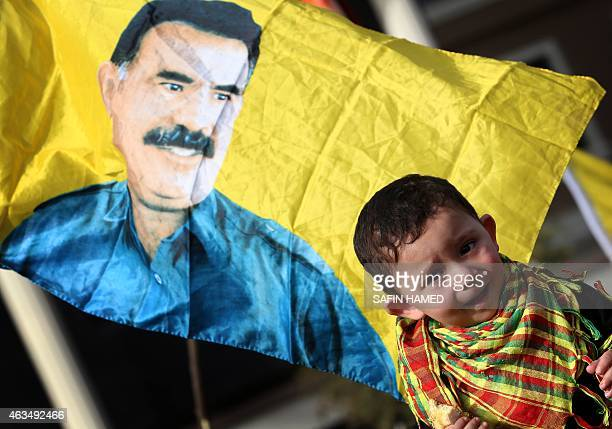 A child is seen in front of a flag bearing a portrait of the leader of the Kurdistan Workers Party Abdullah Ocalan during a demonstration calling for...