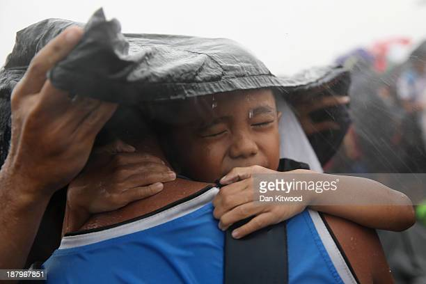 A child is seen trying to take shelter from the rain as they wait for a rescue flight in Tacloban Airport on November 14 2013 in Leyte Philippines...