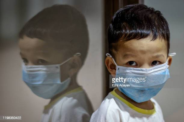 Child is seen wearing a facemask, as public fear over China's Wuhan Coronavirus grows, at the Ninoy Aquino International Airport on February 3, 2020...