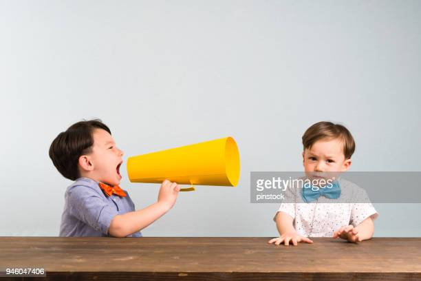 child is shouting through megaphone to another child - megaphone stock pictures, royalty-free photos & images