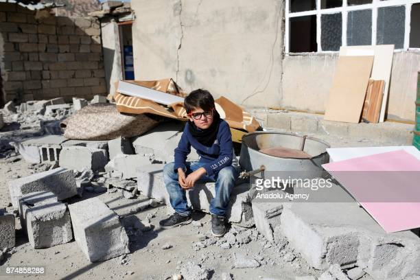 A child is sitting in front of a damaged building at the quakehit area in Bamo village of Halabja district in Sulaymaniyah Iraq on November 16 2017...