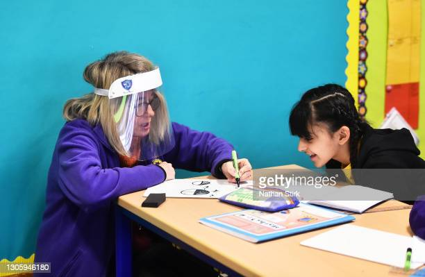 Child is supported with her mathematics work with a teacher wearing a face mask and visor on March 08, 2021 in Stoke on Trent, England. Schools in...