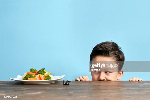 child is very unhappy with having to eat vegetables. - complaining stock pictures, royalty-free photos & images