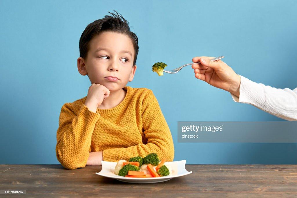 Criança é muito infeliz com a necessidade de comer vegetais. : Foto de stock