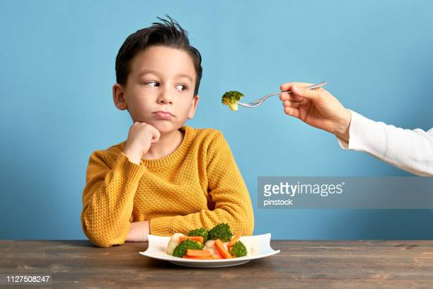 child is very unhappy with having to eat vegetables. - fury stock pictures, royalty-free photos & images