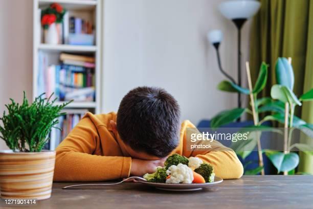 het kind is zeer ongelukkig met het moeten groenten eten. er ligt veel groenten op zijn bord. hij haat groenten. - klagen stockfoto's en -beelden