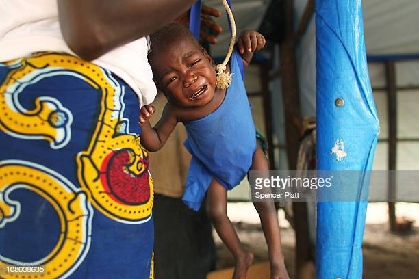 A child is weighed at a malnourishment clinic run by Doctors Without Borders at the Makpandu refugee camp January 14 2011 outside of the town of...