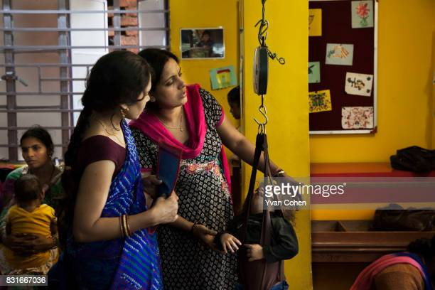 Child is weighed by health workers at a clinic in the Fakir Bagan slum area of Kolkata run by the charity Calcutta Kids. Founded in 2004, Calcutta...