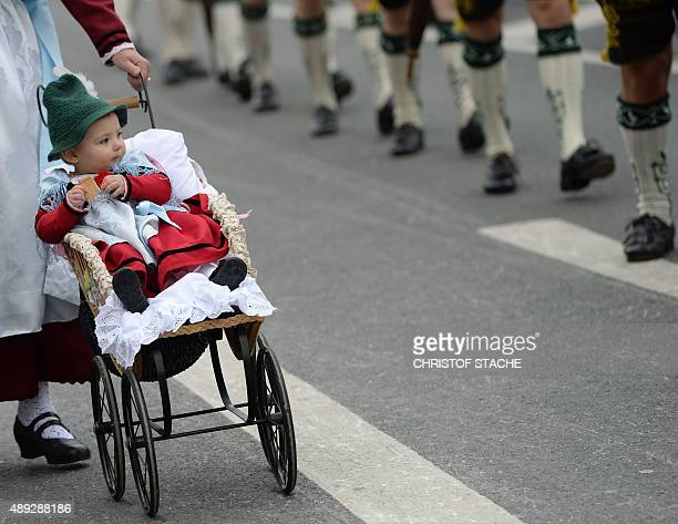 A child is wheeled in a pram during the traditional costume parade at the Oktoberfest beer festival in Munich southern Germany on September 20 2015...