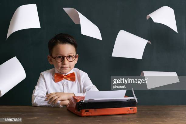 child is writing somethings with typewriter. - authors stock pictures, royalty-free photos & images