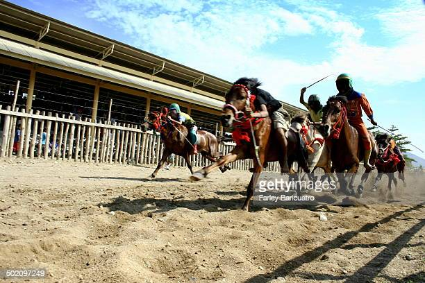 Child jockeys race down the sand track in Bima. The Sunday race is a traditional form of entertainment in remote Bima, Indonesia