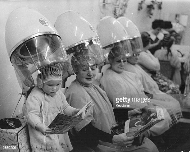 A child joins the older ladies under the hairdryers at the hairdressers