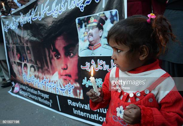 A child joins the Pakistani workers of christian community Revival Church International during a vigil to pay tribute to the victims of the Peshawar...