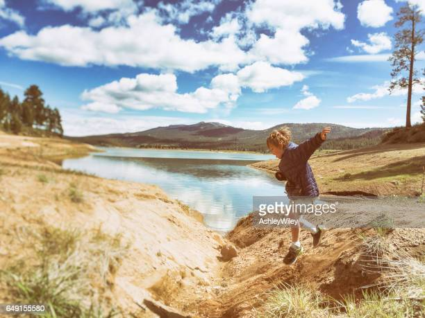 Child jumping and playing outside by lake