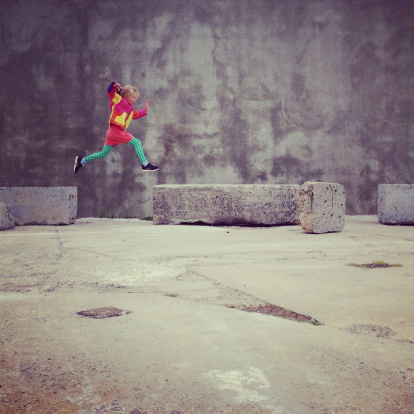 Child jumping from one obstacle to another outside - gettyimageskorea