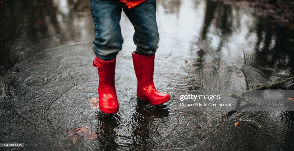 Child jumping in a big puddle : Stock Photo