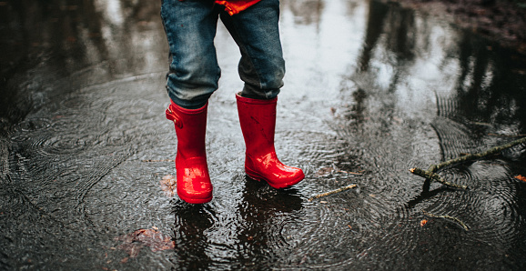 Child jumping in a big puddle - gettyimageskorea