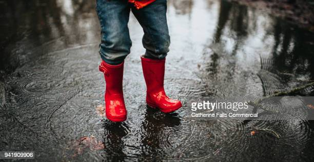 Child jumping in a big puddle