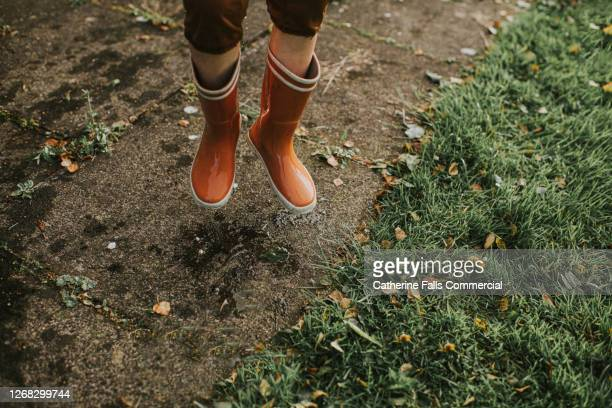 child jumping in bright orange wellies - playing stock pictures, royalty-free photos & images