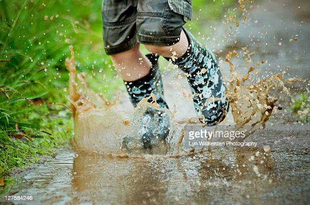 Child jumping in muddy puddle
