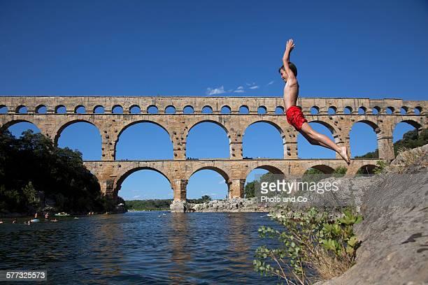child (10 years) jumping into the river - pont du gard stockfoto's en -beelden