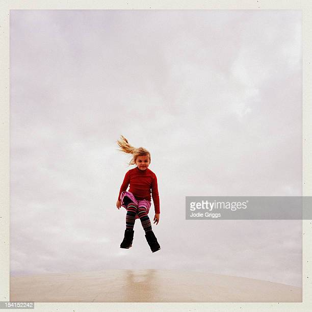 child jumping off dome roof against white clouds - transferbild stock-fotos und bilder