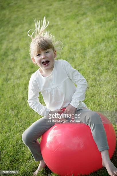 Child jumping on red ball