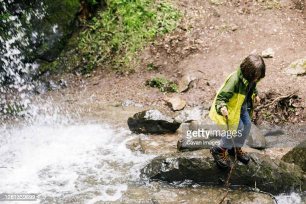 child jumping over rock by river and waterfall - petaluma stock pictures, royalty-free photos & images