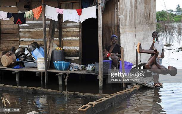 A child jumps from a a flooded house into the water in the town of Yenagoa in the Bayelsa oilrich Niger Delta region on November 15 2012 Nigeria...