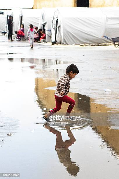 A child jumps in a puddle at a refugee camp after crossing from Syria into Turkey in Suruc September 28 2014 south of Sanliurfa Turkey Islamic State...