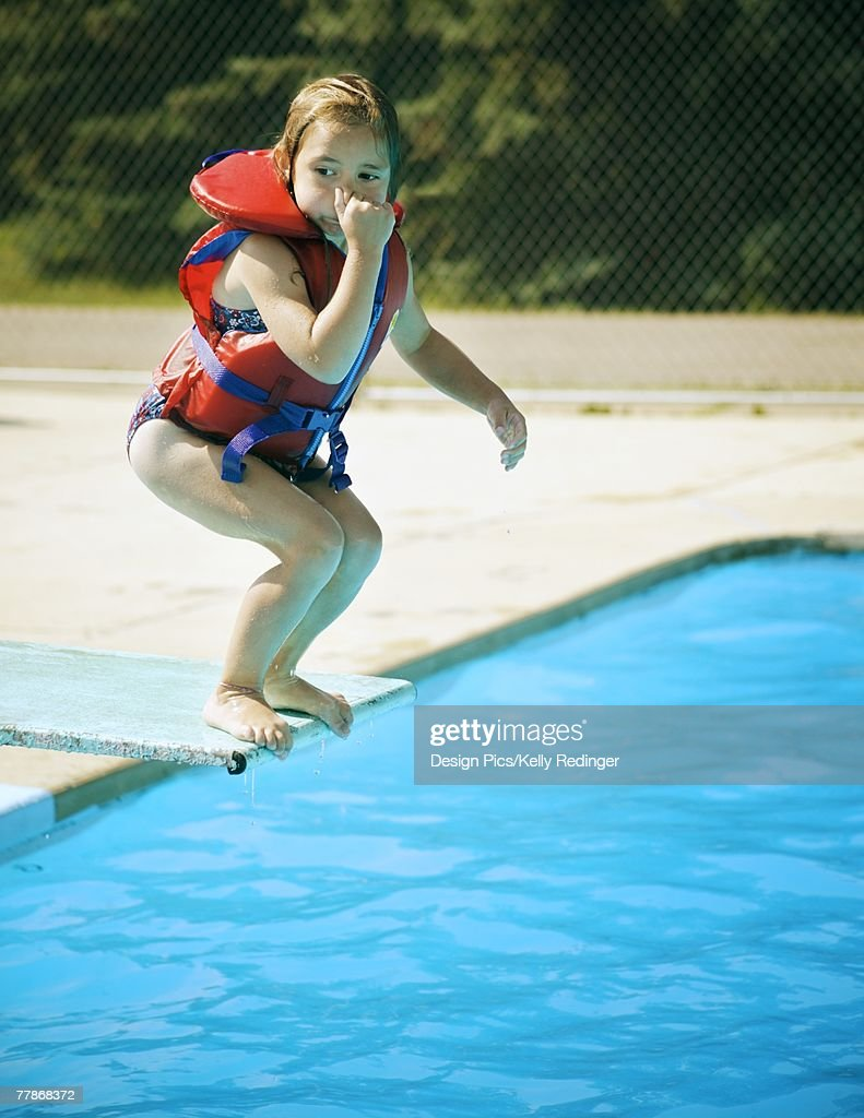A child jumps off diving board : Stock Photo
