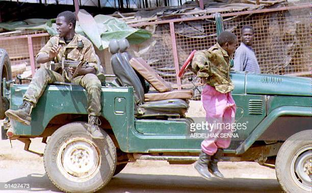 A child jumps out of a car guarded by a militiaman of the governmental forces 15 June 1994 in the center of Kigali The guns fell silent 15 June in...