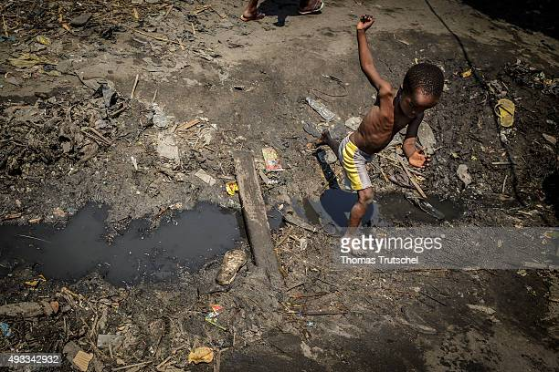 A child jumps over a drainage ditch in a slum in the city of Beira on September 28 2015 in Beira Mozambique