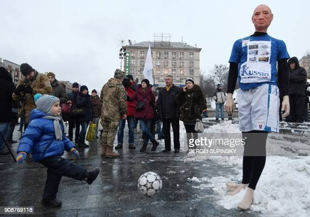 A child kicks a ball at a mannequin depicting Russian President Vladimir Putin dressed in a football uniform during the 'Stop Putin Stop war' rally...