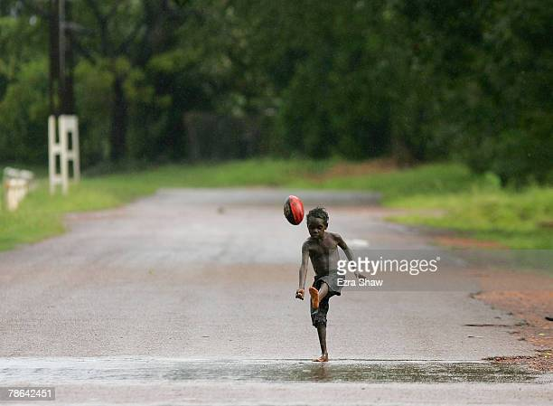 Child kicks the ball down the street after a rain storm cancelled a game of Australian Rules football on December 23, 2007 on the Tiwi Islands,...